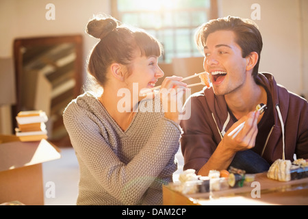 Couple eating sushi together in new home - Stock Photo
