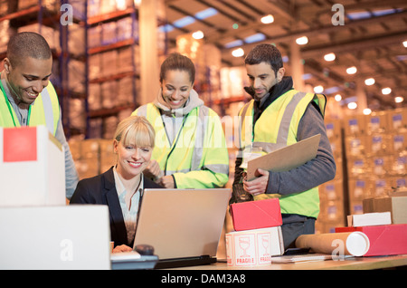 Businesswoman and workers using laptop in warehouse - Stock Photo