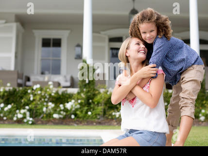 Mother and daughter hugging by swimming pool - Stock Photo