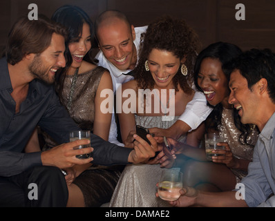 Friends using cell phone at party - Stock Photo