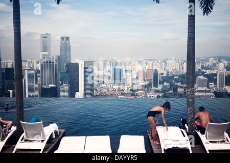 Hotel guests enjoying Singapore's city skyline by the Marina Bay Sand's infinity pool deck - Stock Photo