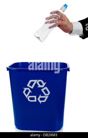 Hand putting an empty water bottle in a blue recycle bin - Stock Photo