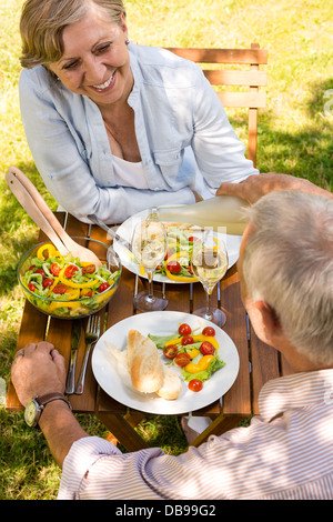 Smiling retired couple eating and drinking outdoors - Stock Photo