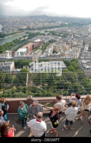 Visitors on the Eiffel Tower looking down on Paris and the River Seine, France. - Stock Photo