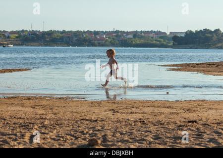Croatia, Dalmatia, Little Boy Playing On Beach - Stock Photo