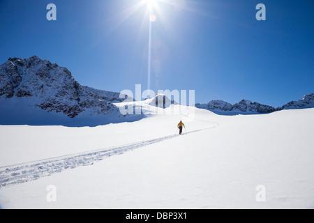 Skier walking across glacier, Stubai, Tyrol, Austria - Stock Photo