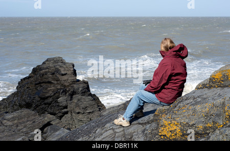 A woman site on some rocks over looking the sea near Tresaith beach in South West Wales on a sunny, yet brisk day. - Stockfoto