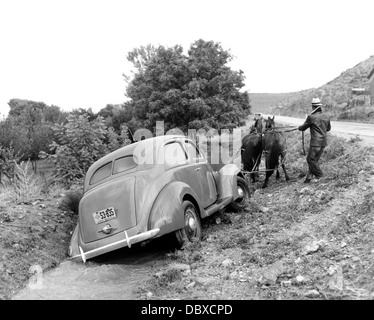 1930s 1937 FORD V-8 BEING PULLED OUT OF RURAL ROAD DITCH BY MAN WITH TEAM OF TWO HORSES - Stock Photo