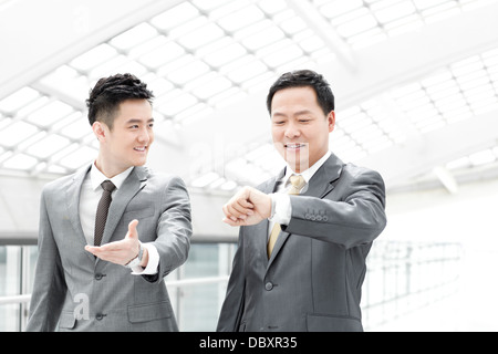 Business people checking the time in airport lobby - Stock Photo