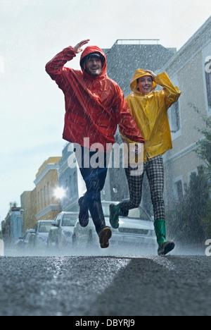 Happy couple in raincoats running down street in rain - Stock Photo