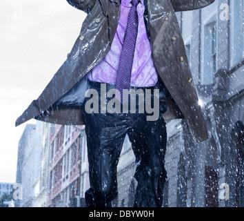 Businessman running in rain - Stock Photo
