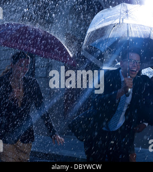 Happy business people running with umbrellas in rain - Stock Photo