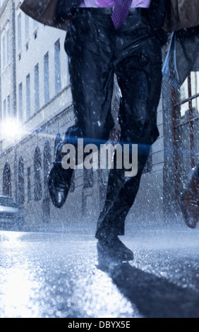 Businessman running in rainy street - Stock Photo
