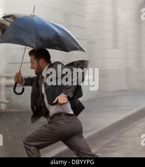 Businessman with umbrella running in rain - Stock Photo