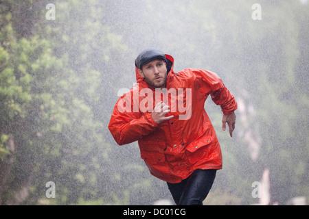 Man in raincoat running in rain - Stock Photo