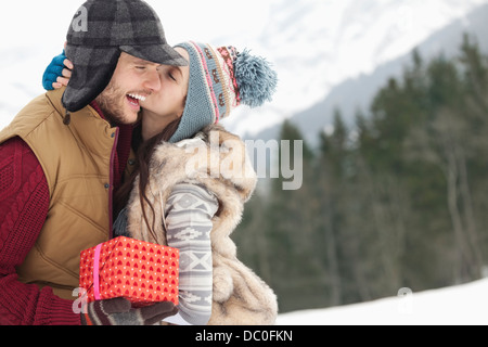 Happy couple with Christmas gift kissing in snowy field - Stock Photo