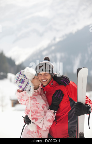 Happy couple with skis kissing in snowy field - Stock Photo