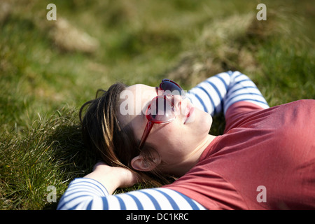 Young woman wearing heart shape sunglasses lying on grass - Stock Photo