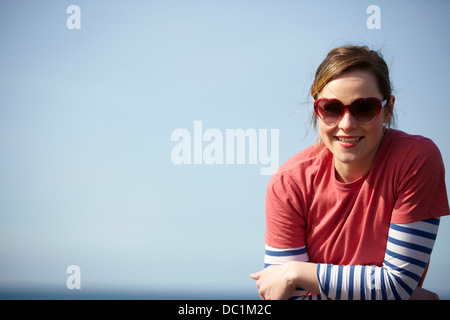 Portrait of young woman wearing heart shape sunglasses at coast - Stock Photo