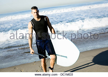 Mid adult man surfer walking on beach with surfboard - Stock Photo