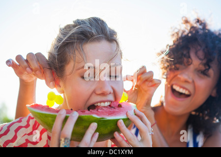 Young woman eating watermelon as friend pulls her ears - Stock Photo