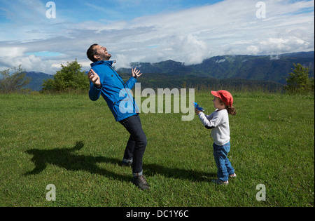Father and young daughter play acting with toy gun - Stockfoto