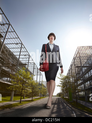 Oversized businesswoman walking on road, low angle view - Stock Photo