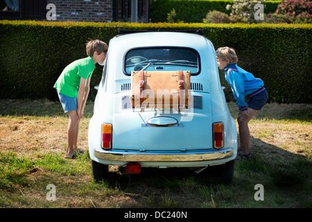 Boys looking through windows of vintage automobile - Stock Photo