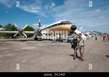 Visitors at Duxford Imperial War Museum. Couple walking along civil aircraft exposition. Bristol Britannia 312 aircraft. - Stock Photo