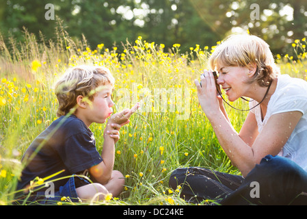 Woman taking photograph of boy blowing kiss - Stock Photo