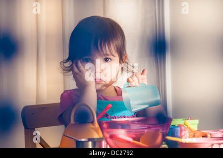 Sad girl playing with toys - Stock Photo