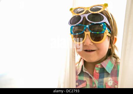 Girl wearing four pairs of sunglasses - Stock Photo