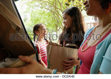 Mother and daughters unloading shopping bags - Stock Photo
