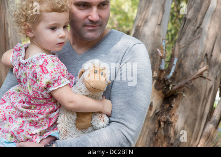 Father carrying child with soft toy - Stock Photo