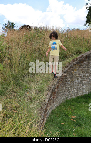 Young boy walking on a wall - Stockfoto