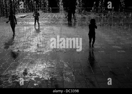 Children play in the fountains in Granary Square, King's Cross, London, UK - Stock Photo