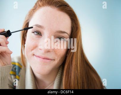 Teenage girl (14-15) applying mascara, studio shot - Stock Photo