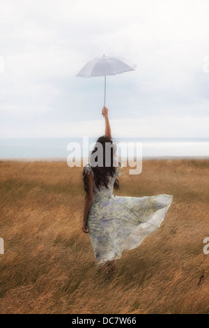 a girl in a floral dress on a field with a parasol - Stock Photo