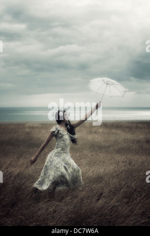 a girl in a floral dress on a field with a parasol is fighting against the wind - Stock Photo