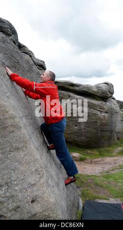 rock climber Doug Blane bouldering at Burbage Edge South, Derbyshire, Peak District National Park, England, UK - Stock Photo