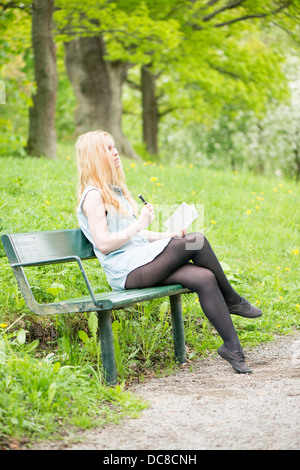 One young attractive woman sitting on bench in a park writing in a diary - Stock Photo