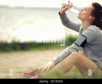 Female runner sitting on the grass while drinking water - Stock Photo