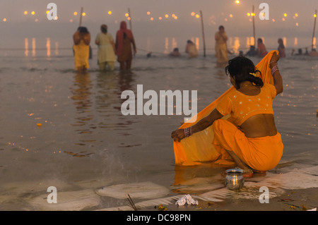 Woman washing her sari in the Sangam, the confluence of the rivers Ganges, Yamuna and Saraswati, Kumbha Mela mass - Stock Photo