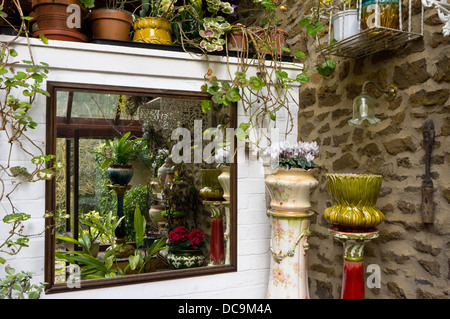 Large square mirror in a UK lean-to conservatory reflecting an arrangement of potted plants and shrubs - Stockfoto