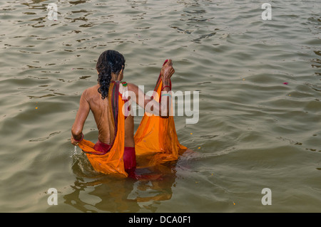 Woman wearing an orange sari taking a bath in the Sangam, the confluence of the rivers Ganges, Yamuna and Saraswati, - Stock Photo