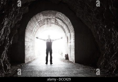 Man stands in dark tunnel with glowing end - Stock Photo