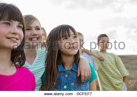 Group of kids standing together outdoors - Stock Photo