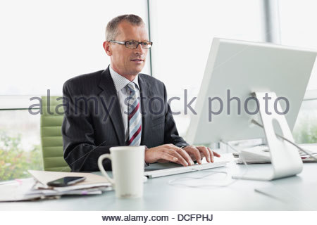 Businessman working on computer in office - Stock Photo
