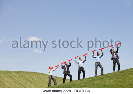 Group of business people implying success with arrows - Stock Photo