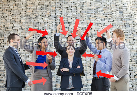 Group of business people pointing arrows towards businesswoman - Stock Photo